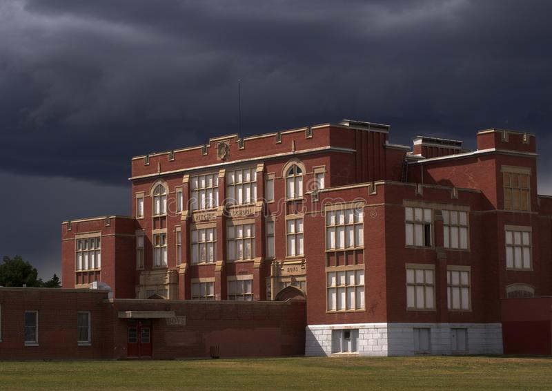 Red Brick School With Dark Storm Clouds. Old red brick school house with dark storm clouds in Edmonton Alberta stock images