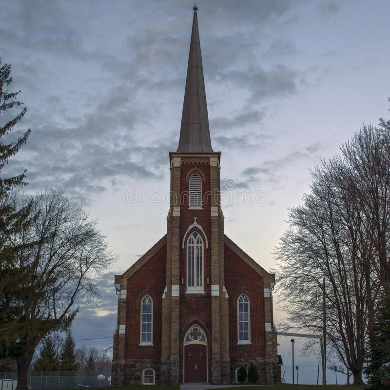 A red brick steeple church at dusk royalty free stock photo
