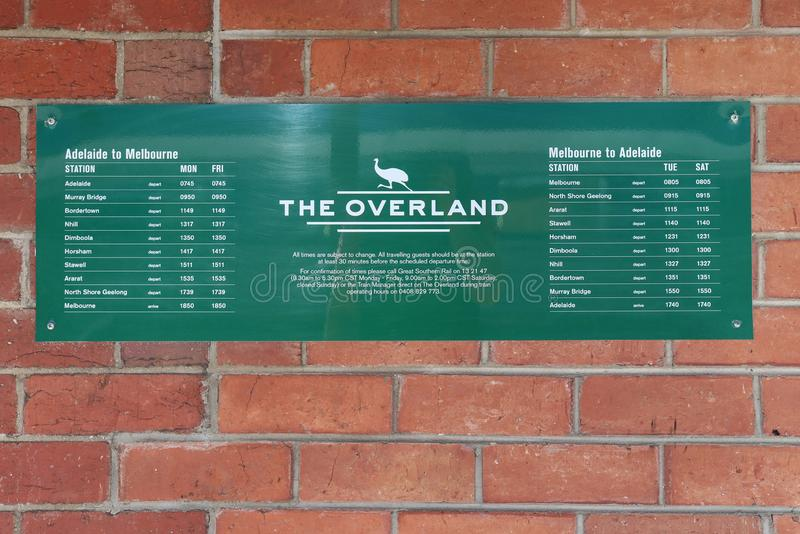 Red brick wall with green and white sign stating The Overland train arrival and departure times royalty free stock photos