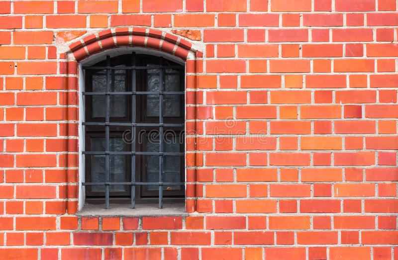 Red brick wall with the iron window grating royalty free stock photography