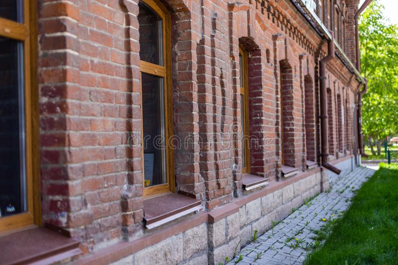 Red brick wall of an old merchant`s house with windows in Novosibirsk, Russia royalty free stock photography