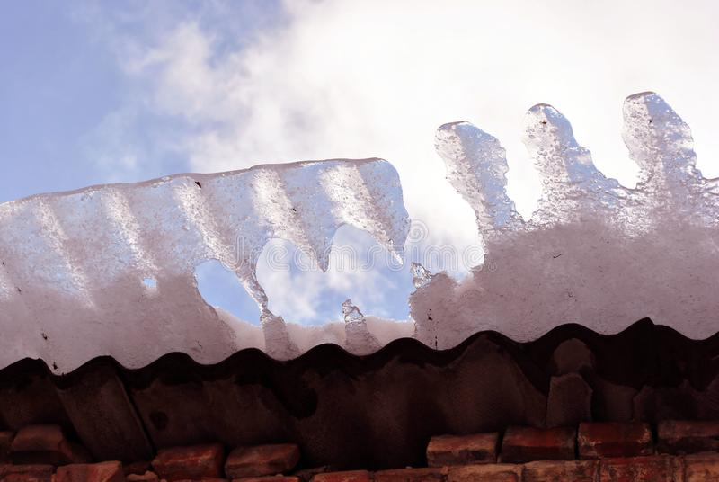 Red brick wall, roof with melting ice falling, view from ground on blue cloudy sky background close up stock images