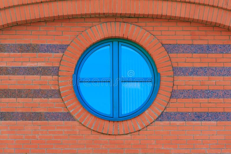 Red brick wall with round glassed window stock image