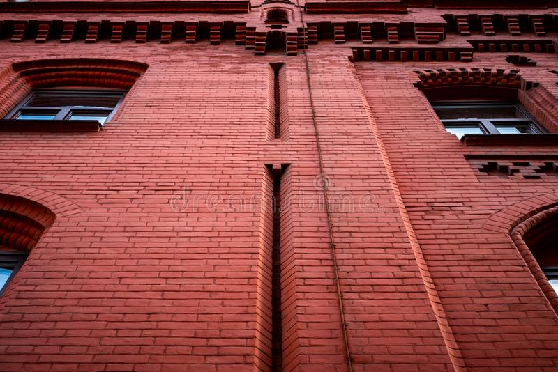 Red brick wall with windows. Bottom view.  stock photos