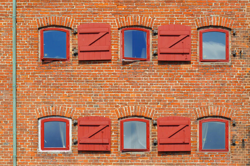 Red brick wall with windows and shutters. Taken in Copenhagen, Denmark royalty free stock photography