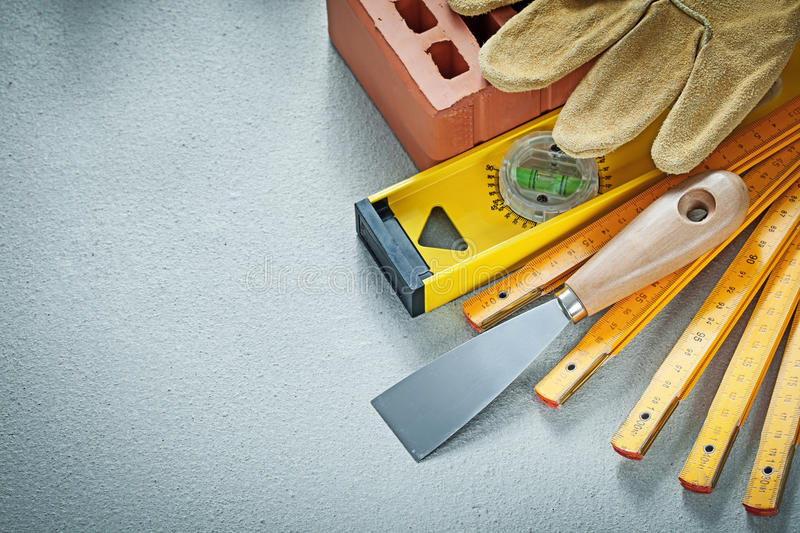Red brick working gloves plastering trowel construction level wo. Oden meter on concrete background bricklaying concept royalty free stock image