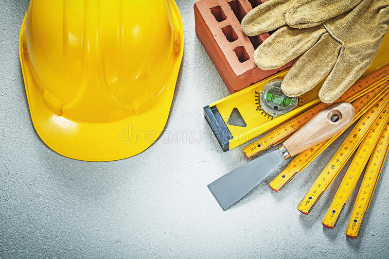 Red brick working gloves plastering trowel construction level wo. Oden meter hard hat on concrete background stock photo