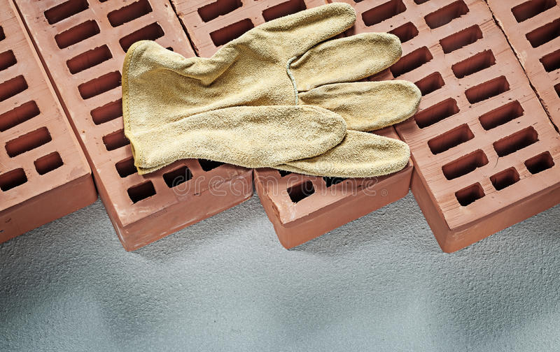 Red bricks leather working gloves on concrete surface constructi. On concept stock image