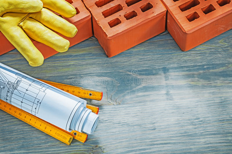 Red bricks leather working gloves construction plans wooden mete. R on wood board bricklaying concept royalty free stock photography