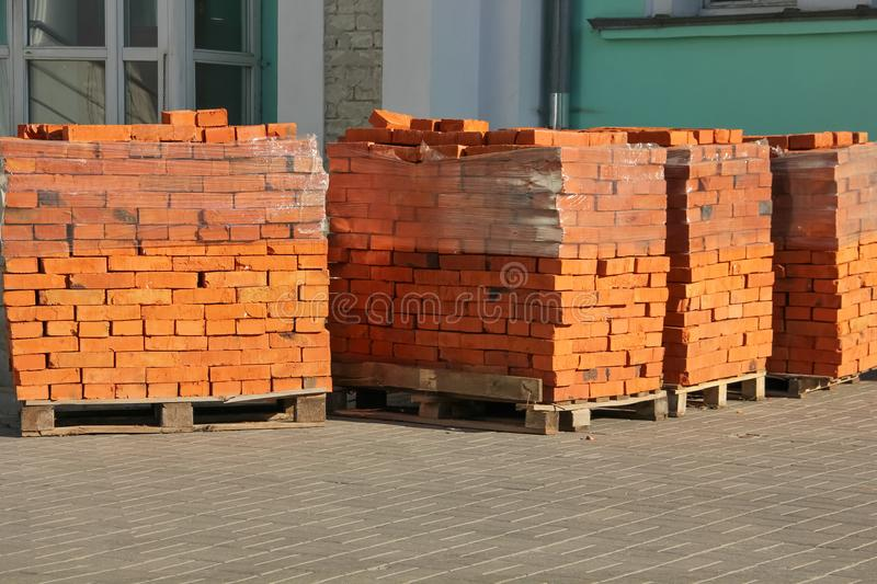 Pallets with red bricks. Red bricks on pallets, wrapped with tape stock photos