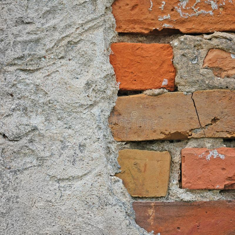 Red bricks stone wall background closeup, cracked ruined stucco, vertical plastered grunge grey beige stonewall limestone pattern royalty free stock photo
