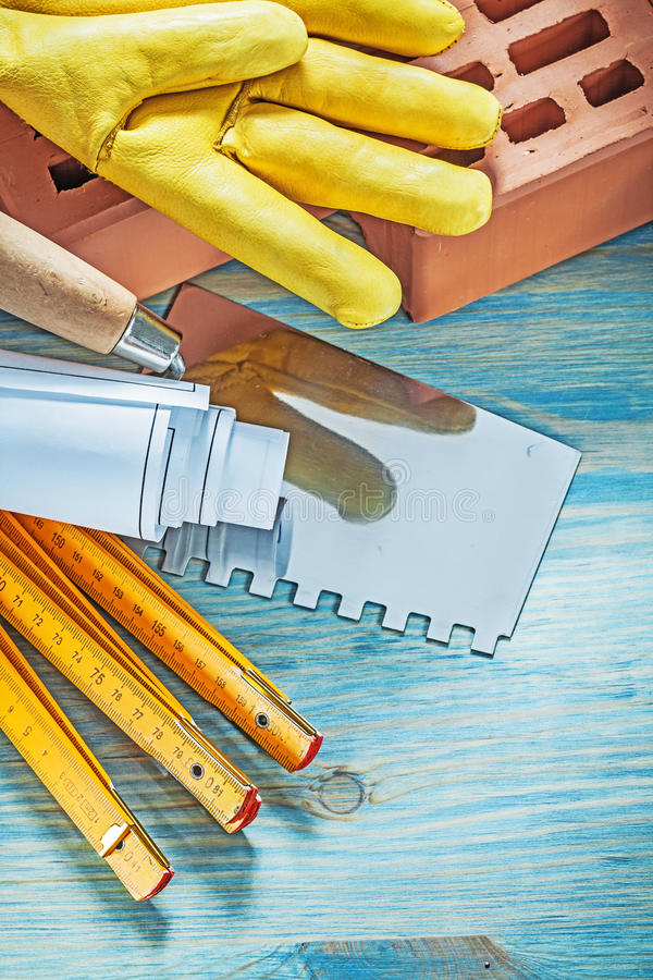 Red bricks working gloves blueprints wooden meter palette knife. On wood board bricklaying concept royalty free stock photos