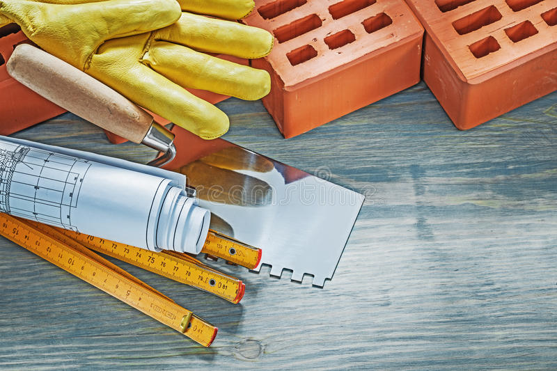 Red bricks working gloves blueprints wooden meter palette plaste. Ring trowel on wood board bricklaying concept stock photos