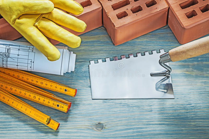 Red bricks working gloves construction drawings wooden meter pal. Ette knife on wood board bricklaying concept royalty free stock photography