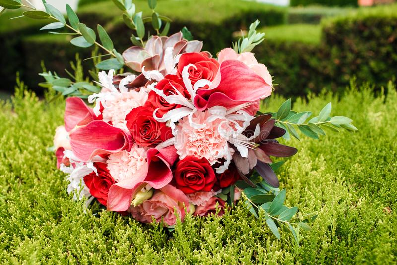 Red bridal bouquet of peonies and roses. Scenery for the wedding. Image royalty free stock photography
