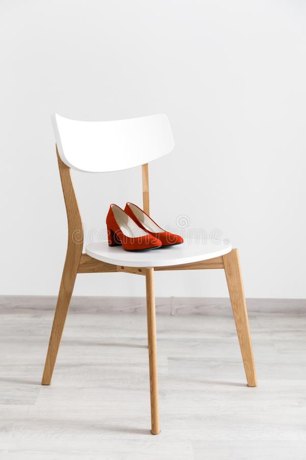 Red bridal shoes with high heels on white chair. Concept of wedding elements and footwear. Red bridal shoes with high heels on white chair stock image