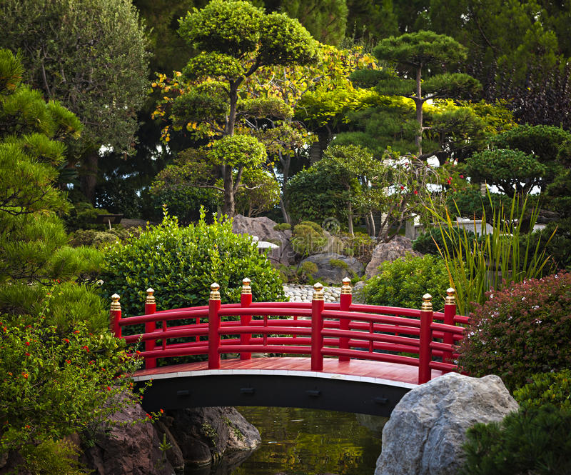 Red bridge in Japanese garden. Red bridge over pond in Japanese garden. Monte Carlo, Monaco royalty free stock photo