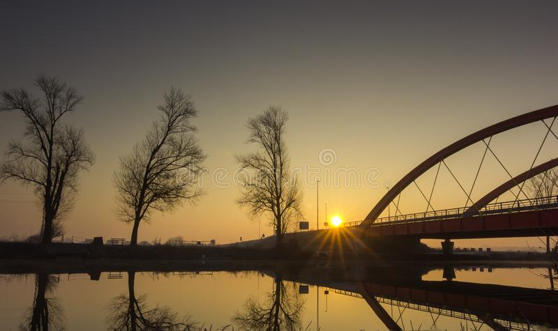Red bridge over the Bosut river in Vinkovci, Croatia. Modern bridge. The sun goes up behind the new bridge over the Bosut River in Vinkovci, Croatia stock photography