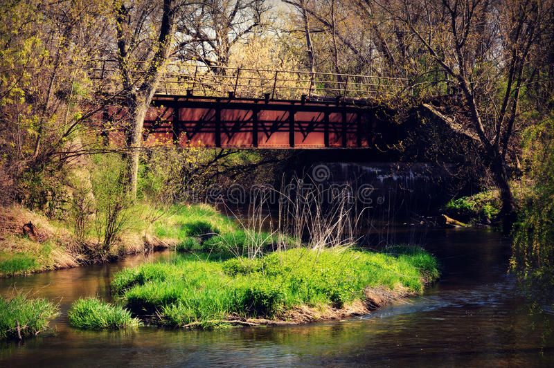 Red Bridge, River, Spring. An old red train bridge crossing the Fox River in Genoa City, Wisconsin in the spring time with everything starting to blossom and stock image
