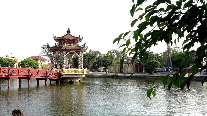 Red bridge and temple on lake stock photography
