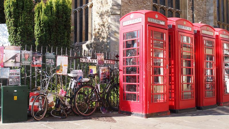 Red British phone boxes and bikes in Cambridge, England. A row of the well-known red British phone box with several bicycles in Cambridge, Great Britain stock photos