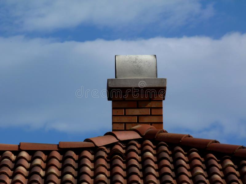 Red brown brick chimneys with white arched concrete cap stone. & metal flashing. terracotta clay roof tiles & vents under clear blue sky with summer sky royalty free stock image