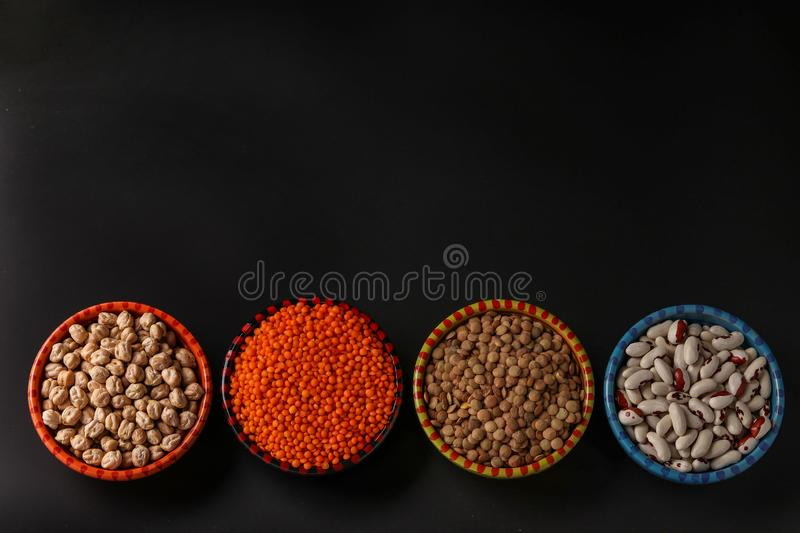 Red and brown lentils, chickpeas and white beans are legumes that contain a lot of protein are located on a dark royalty free stock photos