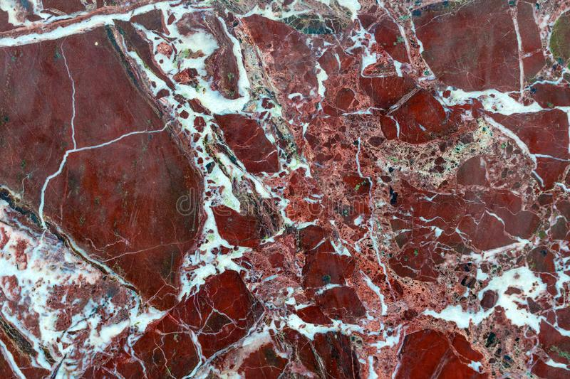 Red, brown marble texture with white streaks stock image