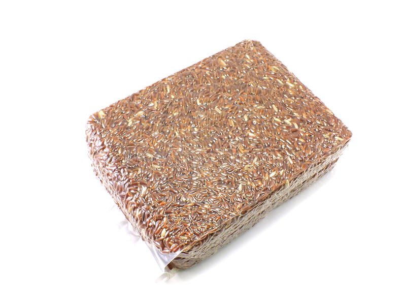 Red brown rice in vacuum package on white background stock image