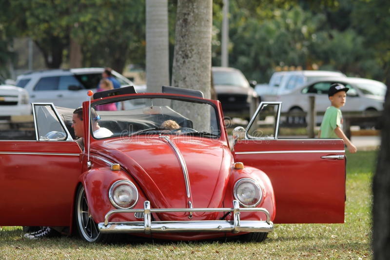 Red buggy. Old convertible Volkswagen Beetle top down and doors opened parked on lawn outdoors on a sunny south Florida day stock image