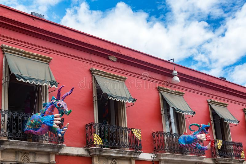 Red Building and Alebrije. Red colonial building and artwork known as alebrije in Oaxaca, Mexico stock images