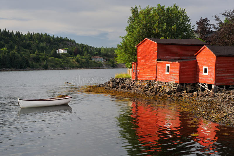 Red building and dinghy. White dinghy in front of red buildings in the harbor at Conception Bay, Newfoundland royalty free stock photos