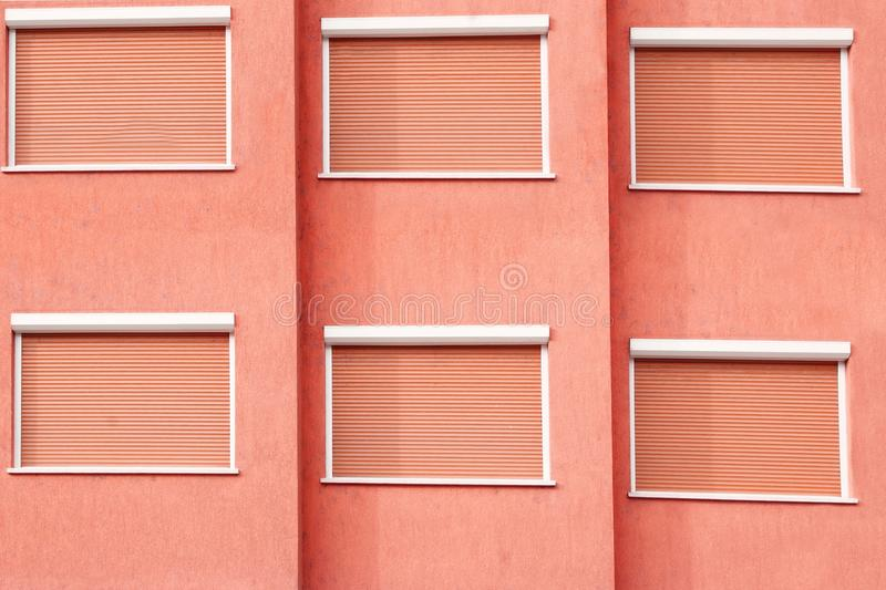 Red Building Facade with Six Closed Windows Shutters. Background with Space for Text or Image royalty free stock photos