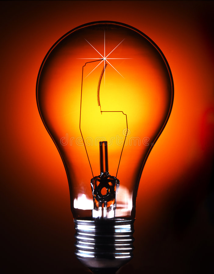 Red bulb. Freestanding lightbulb shot on a gradated red background with starburst on filament royalty free stock images