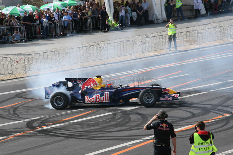 Red Bull que compite con quemadura del coche de carreras foto de archivo