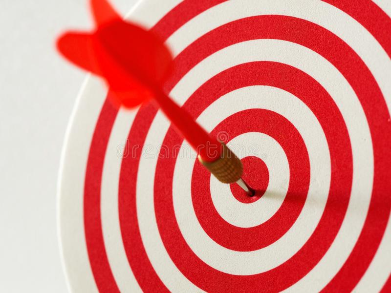 Red bullseye dart arrow hitting target center of dartboard. Concept of success, target, goal, achievement. royalty free stock photos