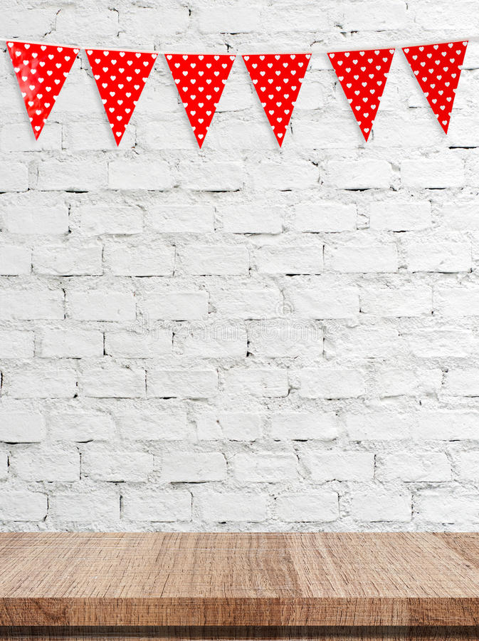 Red bunting party flag with heart shape pattern hanging over empty table background. Valentine`s day concept royalty free stock images