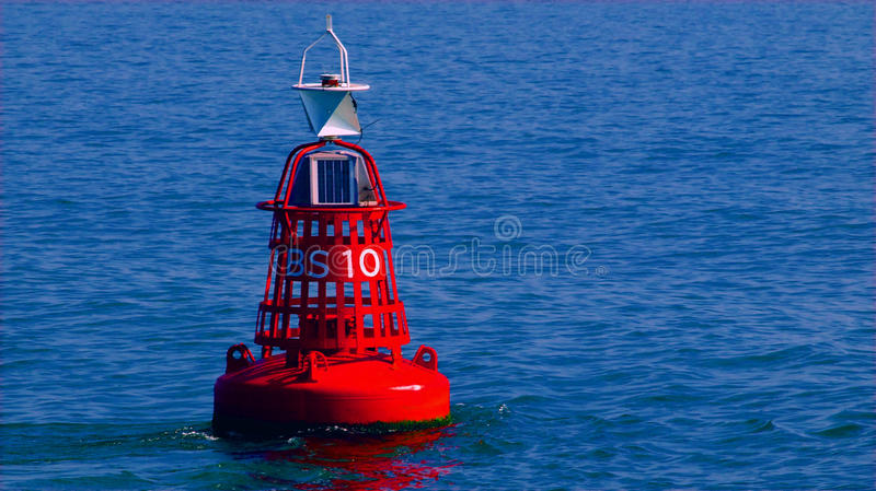 Red buoy. In blue sea stock photos