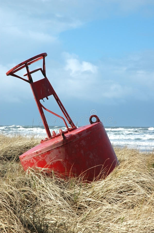 Red Buoy. A large red buoy laying in sea grass on the beach at Long Beach Washington, USA Photo taken on: January 28th, 2006 stock photo