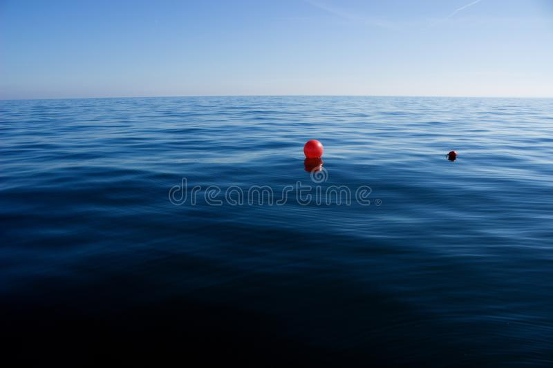 Red buoy on blue sea. Floating calm weather stock photo