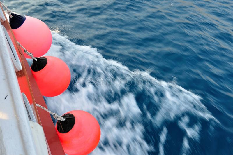 Red buoy on body of moving ship stock photo