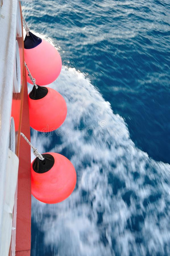 Red buoy on body of moving ship royalty free stock photos