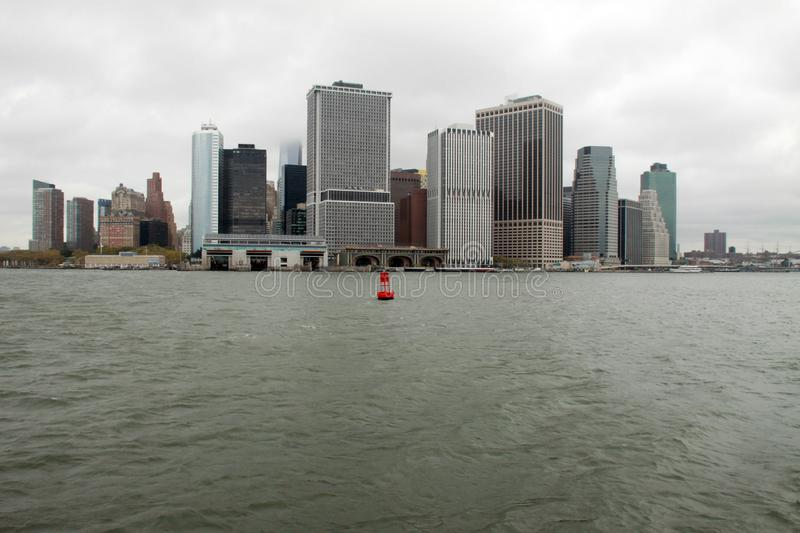 Red Buoy on the East River. Water, cityscape, buildings royalty free stock photography