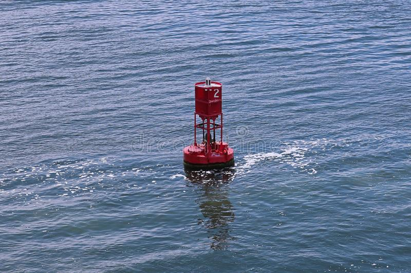 Red buoy in river. Floating red buoy in the river showing navigation and directions royalty free stock photography