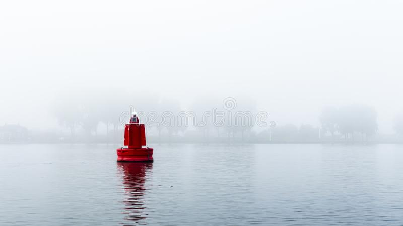 Red buoy in a river in the mist. A red buoy in a river in the mist. The trees in the background are barely visible stock images
