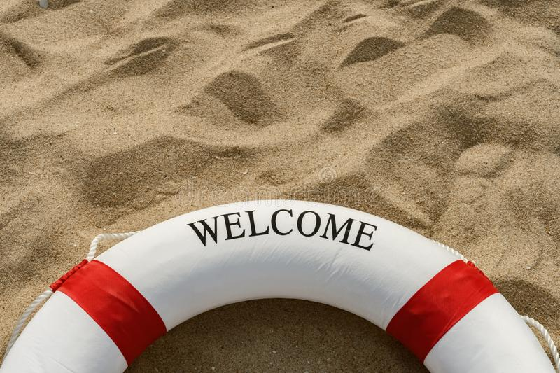 Red buoy on sand with word of welcome. Red buoy on  sand with word of welcome stock image