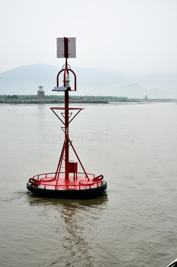 Red buoy with solar panel. Red buoy in grey water with solar cells and autarchical power supply stock photos