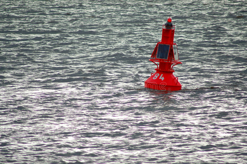 Red buoy with solar panel. Red buoy in grey water with solar cells and autarchical power supply stock images