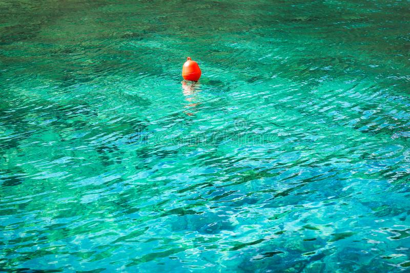 Red buoy in turquoise water. Background, pattern or texture of a red buoy floating on turquoise water. Concept of safe swimming stock photography