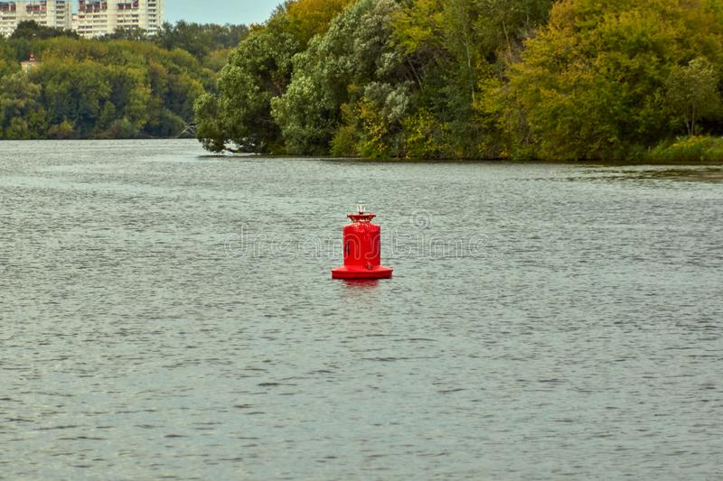 Red buoy. Red warning shipping buoy stands in the middle of a river royalty free stock images
